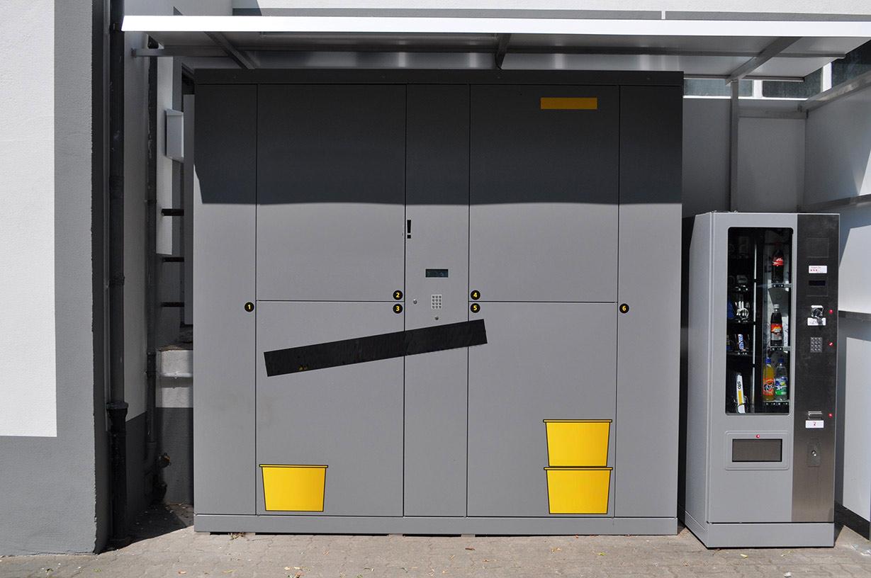 Paketzustellung neu: Paketstation mit integrierter Bedienstation im Außenbereich.